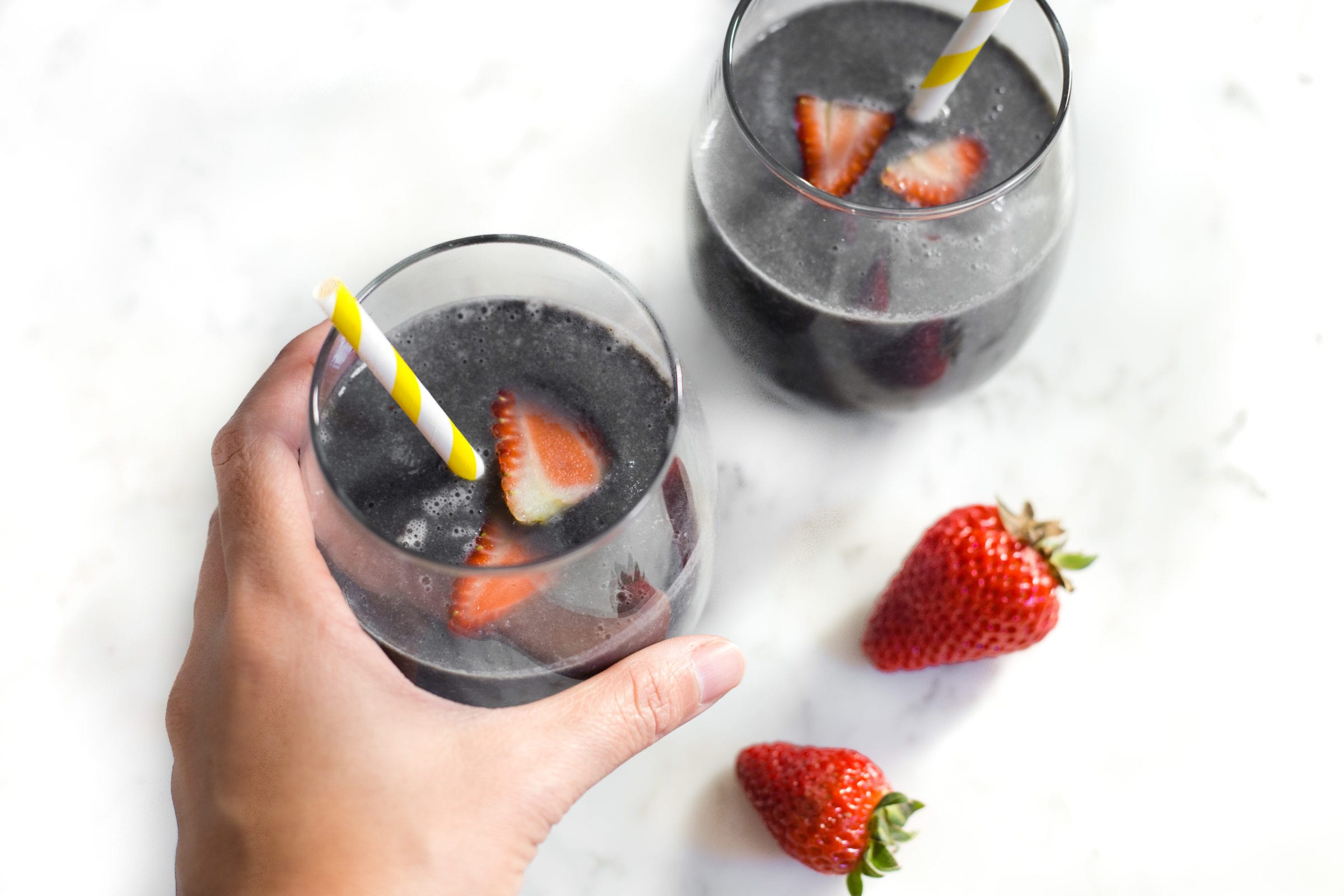 image of two glasses of activated charcoal smoothie with strawberries